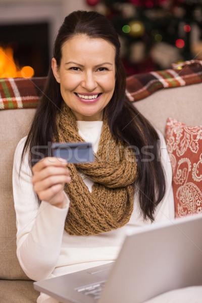 Brunette shopping online with laptop at christmas Stock photo © wavebreak_media