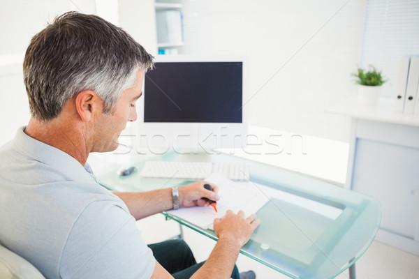 Man with grey hair highlighting information on a document Stock photo © wavebreak_media