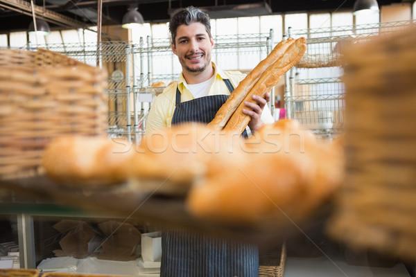 Garçon deux baguettes boulangerie Photo stock © wavebreak_media