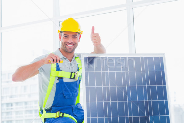 Male worker tightening solar panel while gesturing thumbs up Stock photo © wavebreak_media