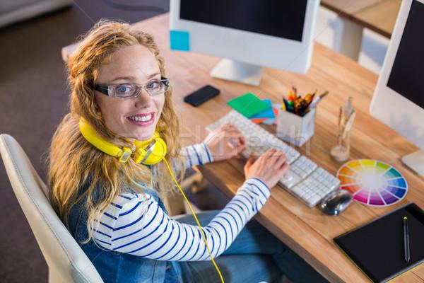 Mosolyog designer gépel billentyűzet iroda üzlet Stock fotó © wavebreak_media
