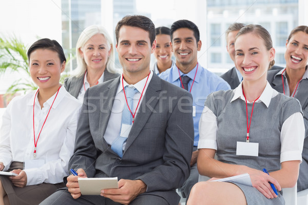 Stock photo: Smiling business people looking at camera during meeting