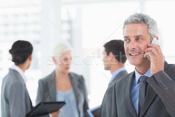 бизнесмен смартфон коллеги за служба женщину Сток-фото © wavebreak_media