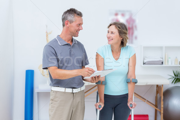 Woman using crutch and talking with her doctor Stock photo © wavebreak_media