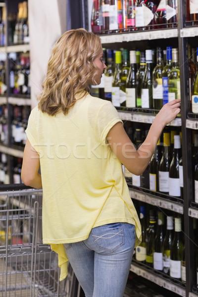 Hátulnézet szőke nő néz borosüveg áruház üzlet Stock fotó © wavebreak_media
