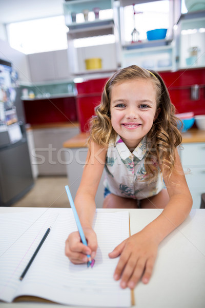 Portret uśmiechnięty dziewczyna praca domowa kuchnia domu Zdjęcia stock © wavebreak_media