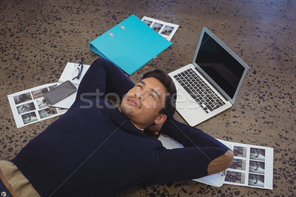 Thoughtful businessman lying by laptop and photographs at office Stock photo © wavebreak_media