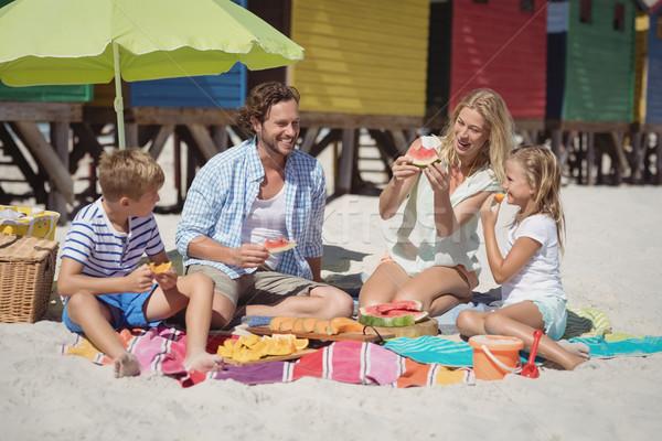 Família feliz alimentação melancia sessão juntos praia Foto stock © wavebreak_media