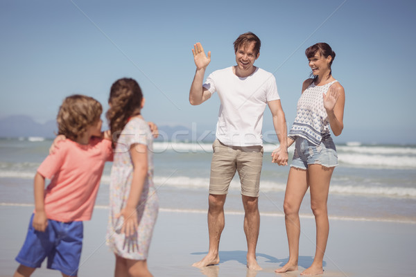 Happy parents waving hands while looking at children standing on shore Stock photo © wavebreak_media