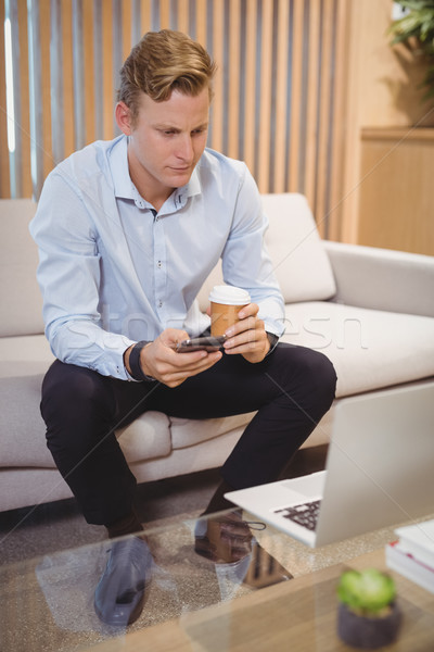 Attentive executive using mobile phone while having coffee Stock photo © wavebreak_media