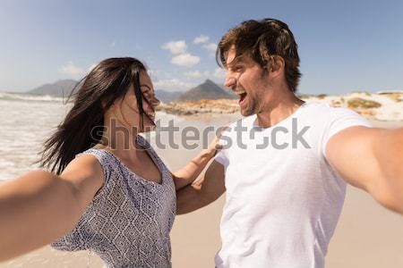 Side view of couple practicing meditation at beach Stock photo © wavebreak_media