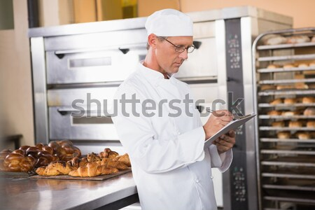 Female chef looking at an order list in the commercial kitchen Stock photo © wavebreak_media