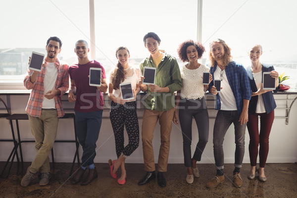 Portrait of smiling business team showing technologies at creative office Stock photo © wavebreak_media