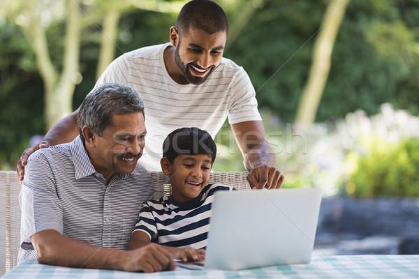 Szczęśliwy rodziny za pomocą laptopa weranda wraz tabeli Zdjęcia stock © wavebreak_media