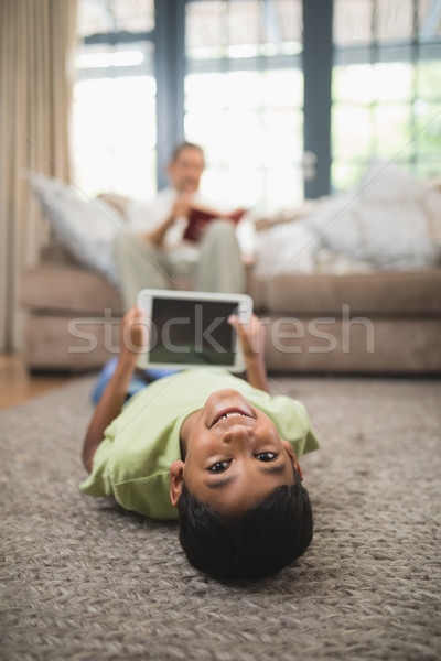 Portrait of boy holding digital tablet while lying on carpet Stock photo © wavebreak_media