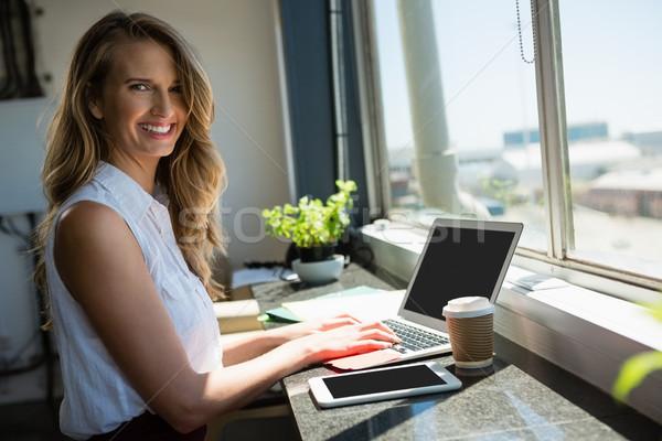 Stock photo: Portrait of smiling businesswoman using laptop