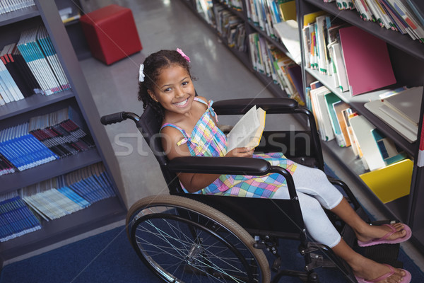 Portrait of smiling girl with book on wheelchair Stock photo © wavebreak_media
