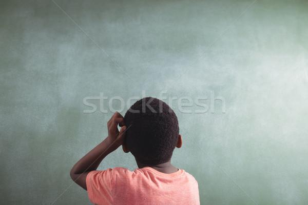 Rear view of thoughtful boy against greenboard Stock photo © wavebreak_media