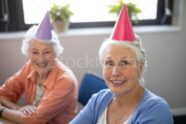Portrait of smiling senior friends wearing party hats Stock photo © wavebreak_media