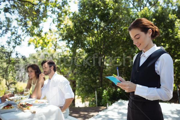 Sorridere cameriere iscritto fine notepad amici Foto d'archivio © wavebreak_media