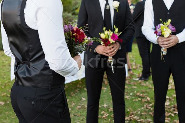 Bridegroom and best man standing with bouquet of flowers in garden Stock photo © wavebreak_media