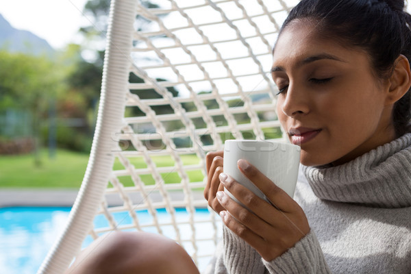 Woman holding coffee cup in swing chair Stock photo © wavebreak_media