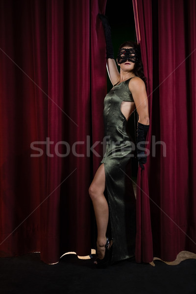 Female artist in masquerade mask posing in front of massive red stage curtain Stock photo © wavebreak_media