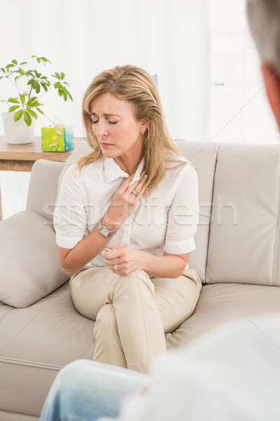 Unhappy woman sitting on couch and talking to therapist  Stock photo © wavebreak_media
