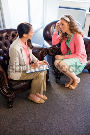 Female teacher using digital tablet while students talking in background Stock photo © wavebreak_media