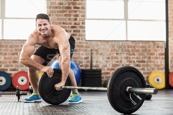 Muscular man set up his barbell weight Stock photo © wavebreak_media