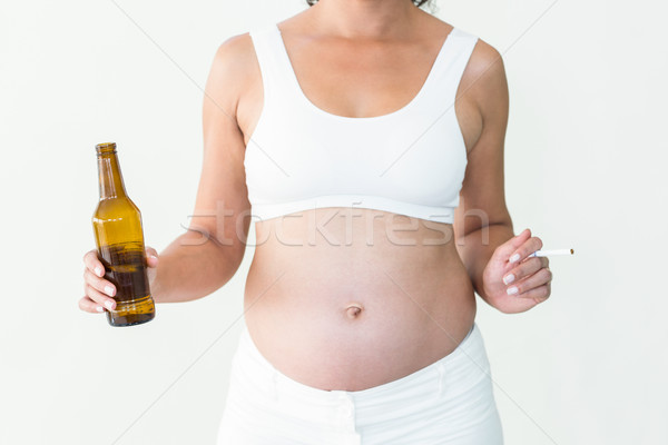 Pregnant woman holding cigarette and beer bottle Stock photo © wavebreak_media