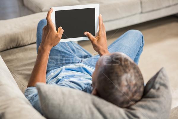 Over shoulder view of casual man using tablet Stock photo © wavebreak_media