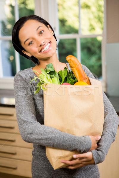 улыбаясь брюнетка продуктовых сумку кухне Сток-фото © wavebreak_media