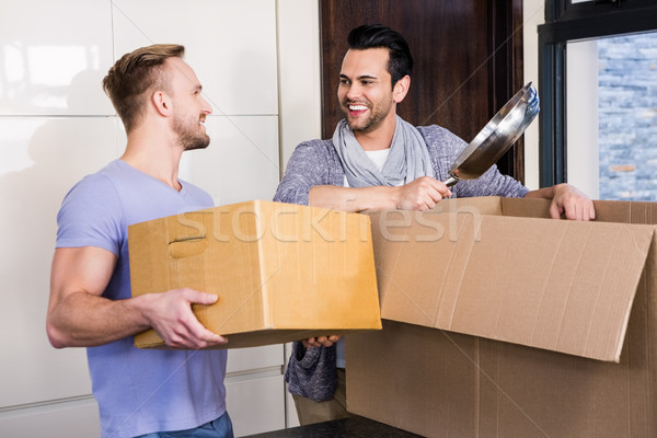 Smiling gay couple unpacking cardboard Stock photo © wavebreak_media