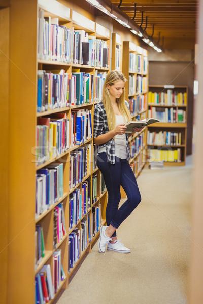 Estudante leitura livro prateleira de livros biblioteca Foto stock © wavebreak_media