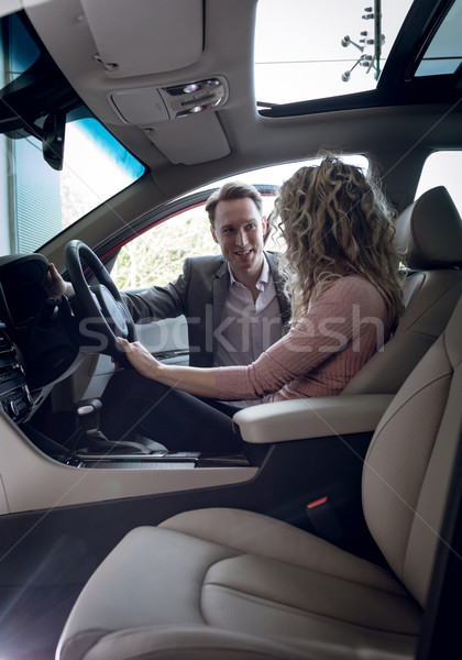Stock photo: Smiling salesman talking to female customer sitting in car