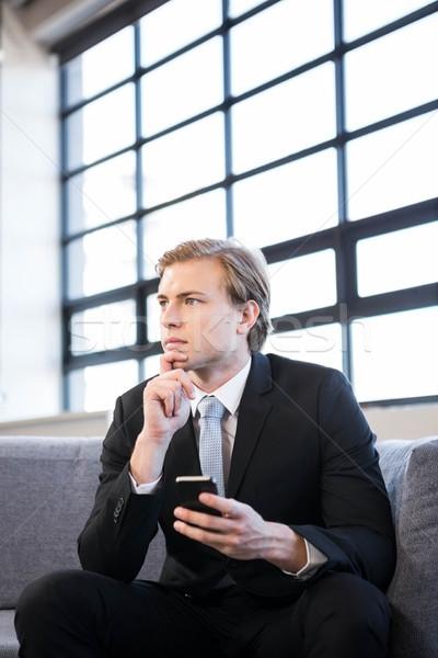 Figyelmes üzletember ül kanapé másfelé néz iroda Stock fotó © wavebreak_media