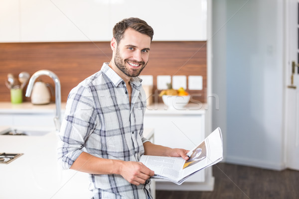 Stock photo: Man holding newspaper while leaning on kitchen counter