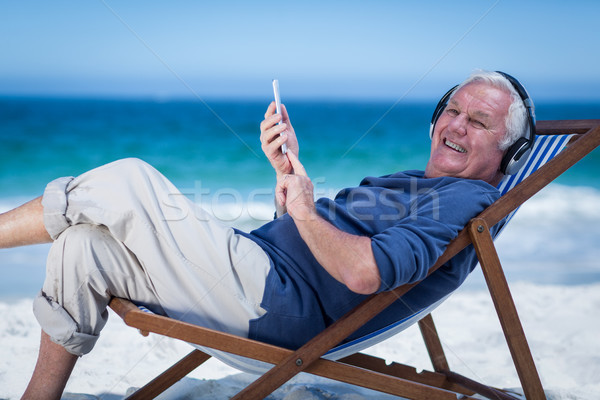 Mature man resting on a deck chair listening to music with smart Stock photo © wavebreak_media