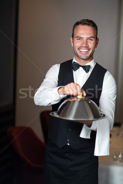 Handsome waiter holding tray Stock photo © wavebreak_media
