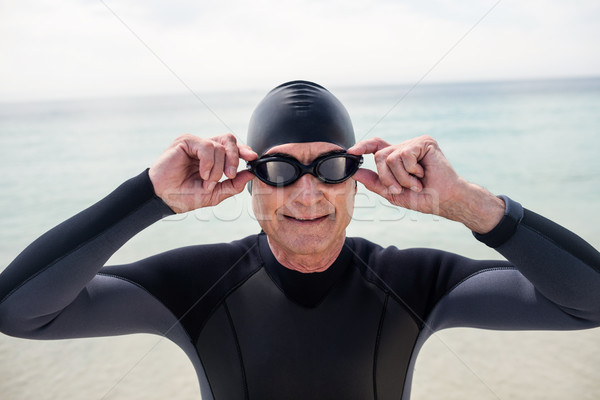 Senior man in wetsuit and swimming goggles standing on beach Stock photo © wavebreak_media