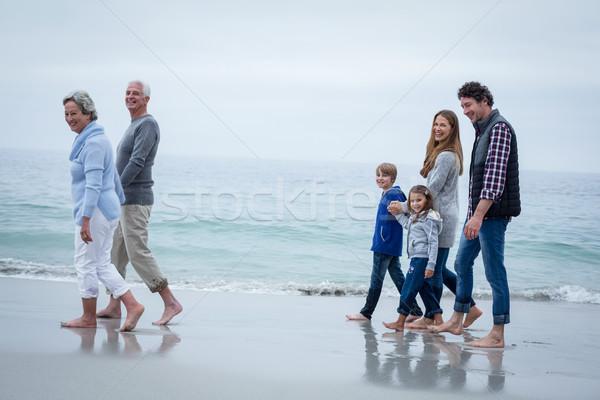 Cheerful multi-generation family walking at sea shore Stock photo © wavebreak_media