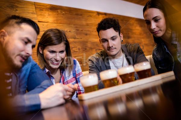 Friends looking at beer glasses in restaurant Stock photo © wavebreak_media