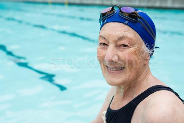 Smiling senior woman sitting at poolside Stock photo © wavebreak_media