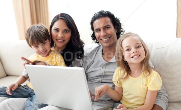 Jolly family using laptop on sofa Stock photo © wavebreak_media