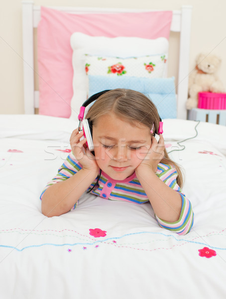 Mooie weinig luisteren naar muziek hoofdtelefoon bed gelukkig Stockfoto © wavebreak_media