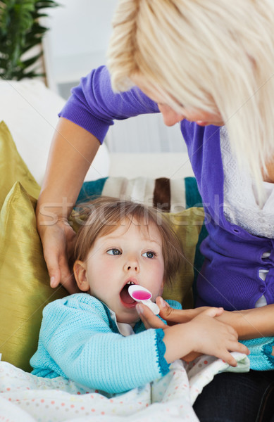 Sick little girl getting syrup from her caring mother at home Stock photo © wavebreak_media