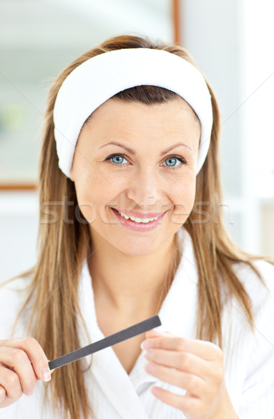 Captivating woman using a nail file wearing a bath robe standing in the bathroom Stock photo © wavebreak_media