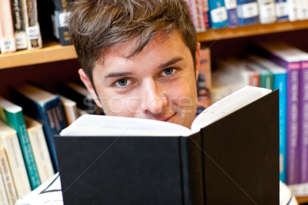 Portrait of a good-looking male student reading a book sitting on the floor Stock photo © wavebreak_media
