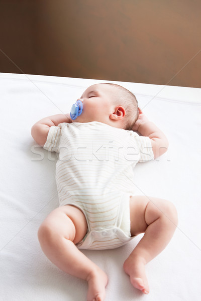 Portrait of a sweet baby with a pacifier sleeping on the sofa in the living-room at home Stock photo © wavebreak_media